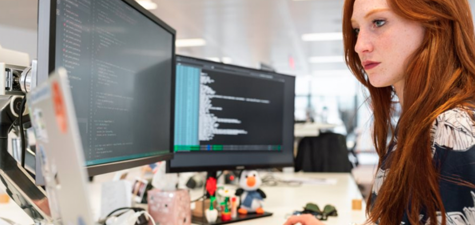 Red haired girl infront of two computer screens