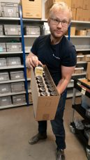 Johan Axelsson står i ett rum med hyllor fulla av frölådor och håller i en pappbox med fröprover.