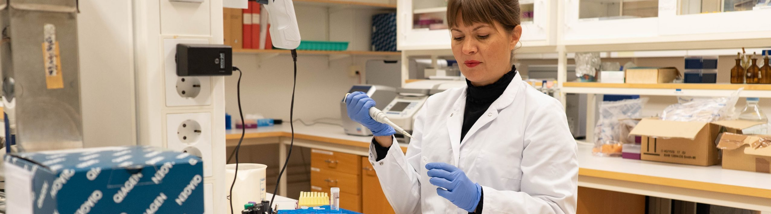 Kvinna står i vit labrock och använder pipett i NordGens molekylärlaboratorium