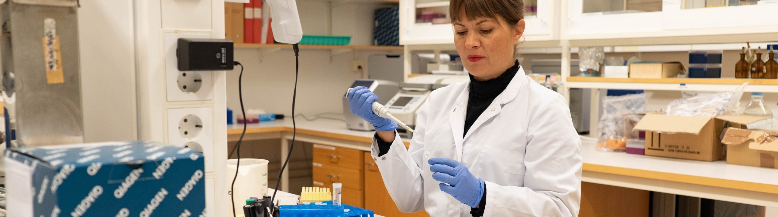Woman standing in a lab coat and gloves in a molecular laboratory performing experiments.