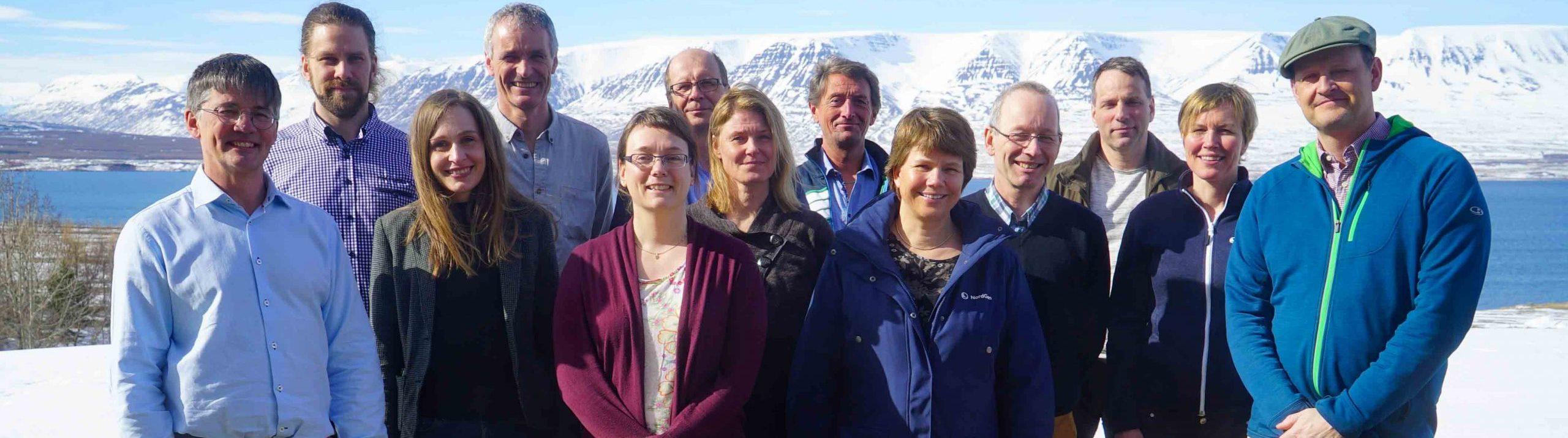 Medlemmarna i skogsrådet står framför en snötäckt bergskedja.