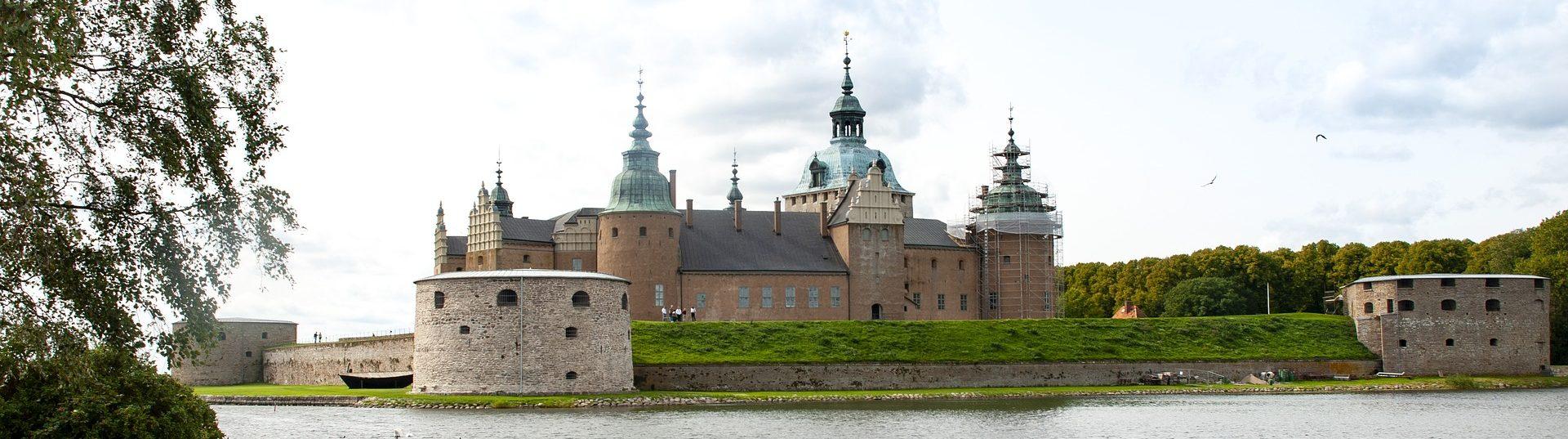 Bild på Kalmar slott med vatten i förgrunden.