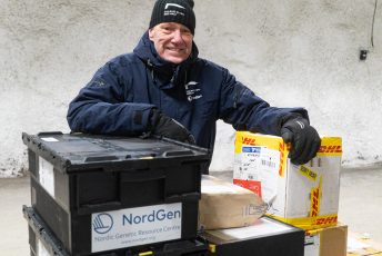 NordGen's Seed Vault Coordinator Åsmund Asdal standing inside the Svalbard Global Seed Vault leaning towards seed boxes from different genebanks.