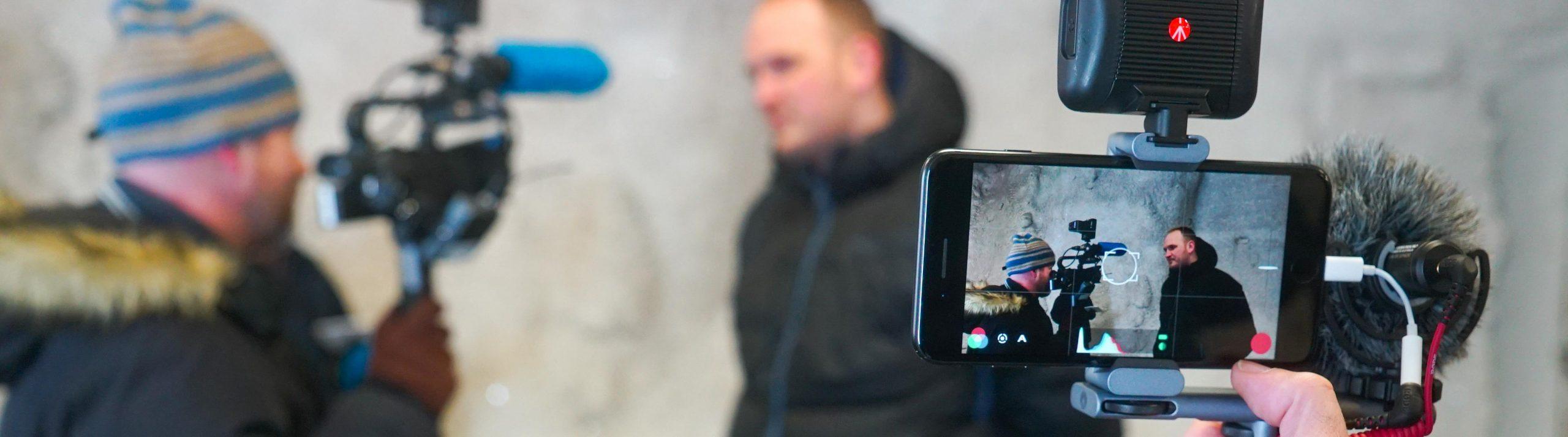 En mobilkamera med mikrofon filmar en man som intervjuas av en annan man med kamera