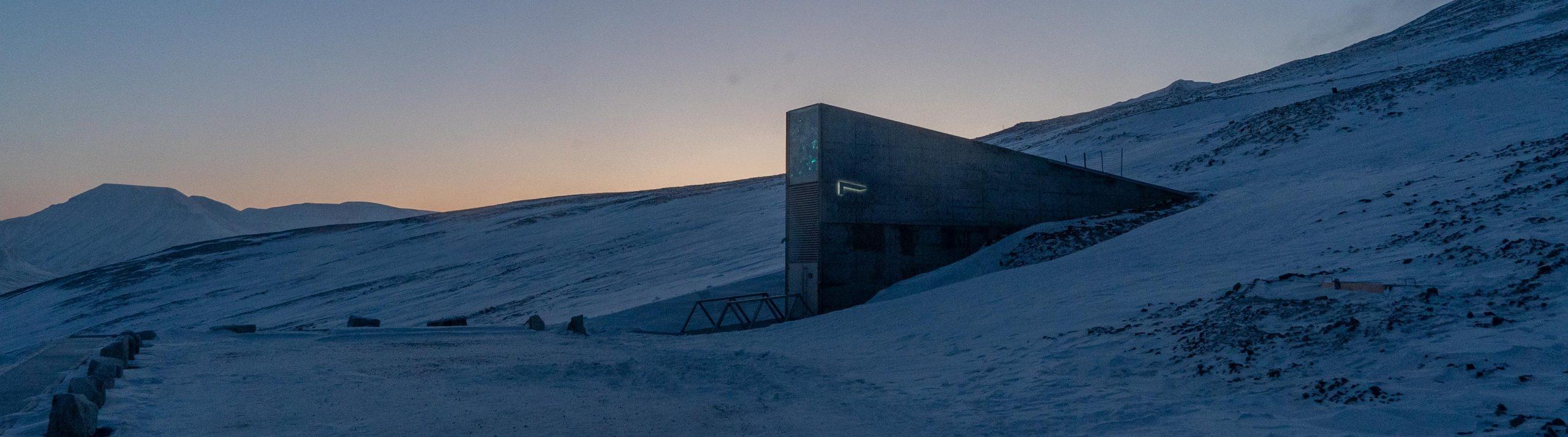 Ett vinterlandskap med avlägsen soluppgång och en trekantig betongbyggnad i förgrunden