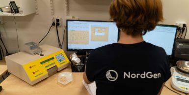 Kvinna i NordGen-tröja sitter och arbetar framför två datorskärmar med databassytemet SESTO.