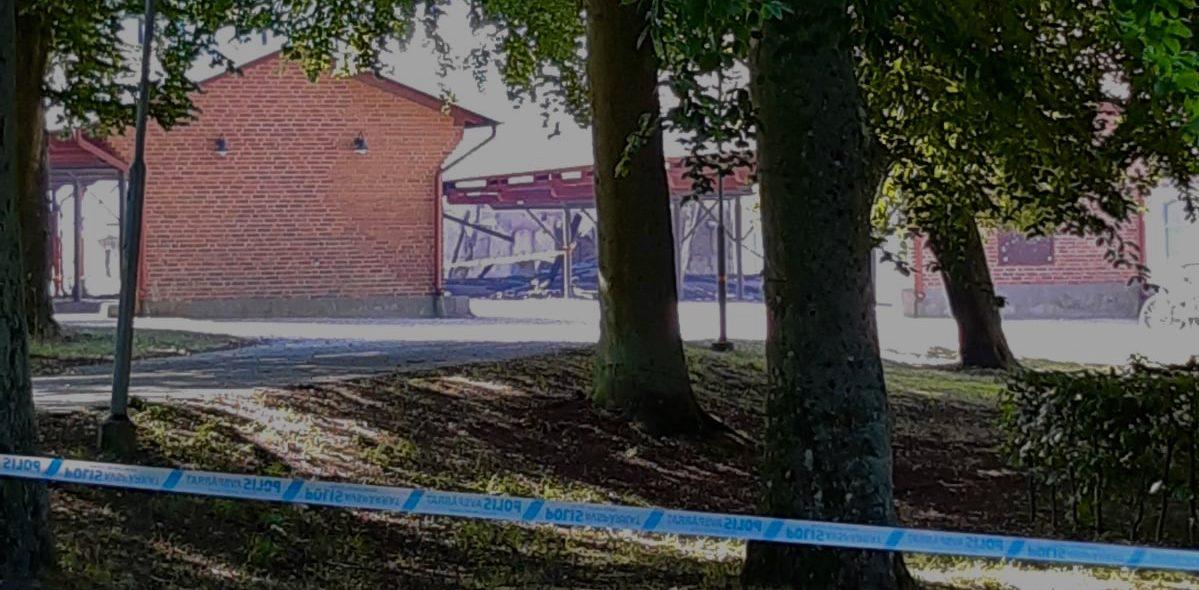 Polisband framför träd och en utbränd byggnad
