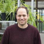 Noam Chayut, chef för GRU vid John Innes Centre tittar in i kameran med växter i bakgrunden