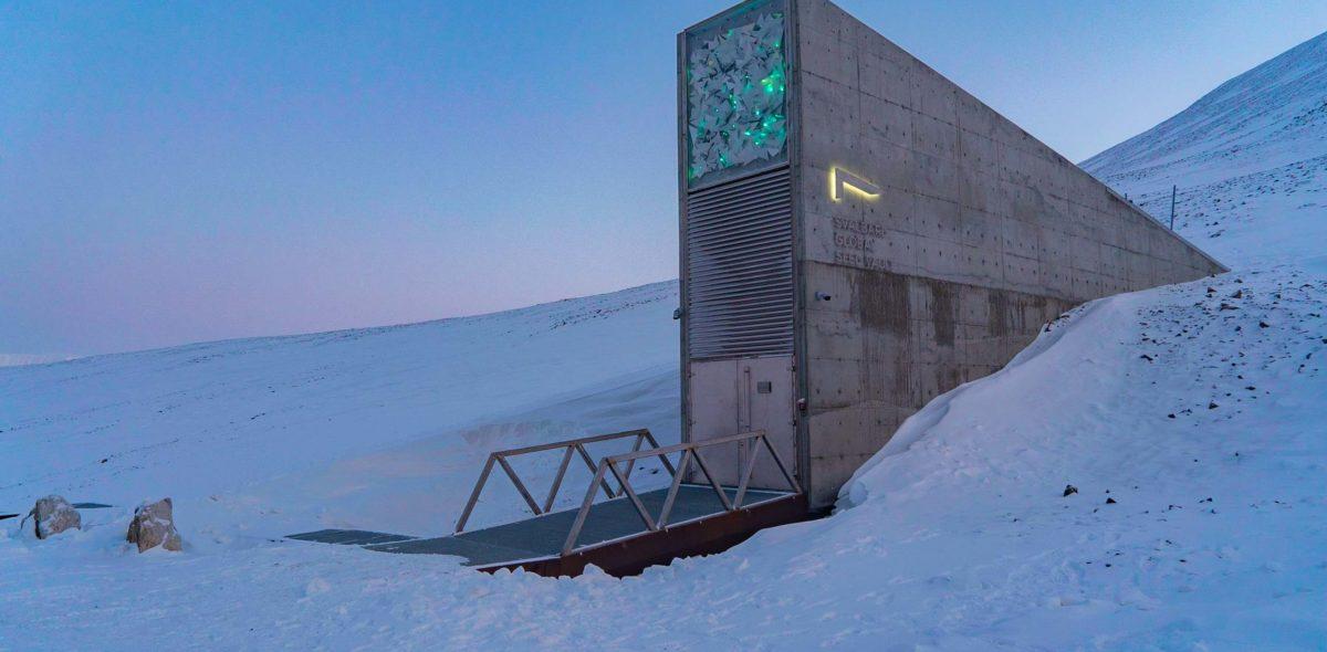 Bild på Svalbard Global Seed Vault omgivet av snö och en ljusblå himmel.