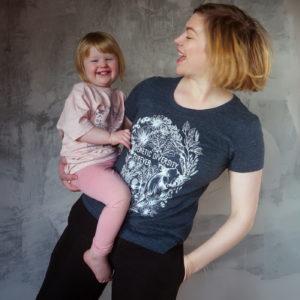 Kvinna med barn i famnen framför en betongvägg. Båda  bär på t-shirt med tryck där det står Genetic Diversity Forever