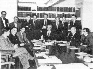 En svartvit bild på en grupp med många män och en ensam kvinna som sitte och står r runt ett bord.