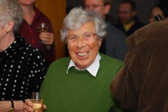 En äldre kvinna i grön tröja håller i ett glas och ler mot kameran.