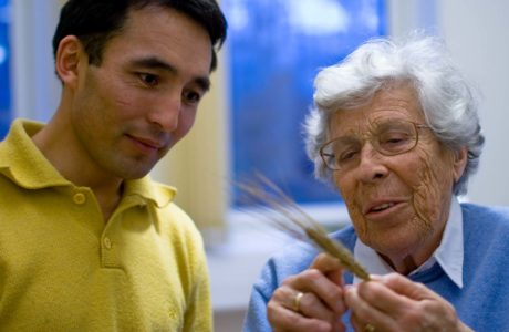 A young man in a yellow shirt looking at a barley straw and listening to an elderly woman in blue shirt and glasses