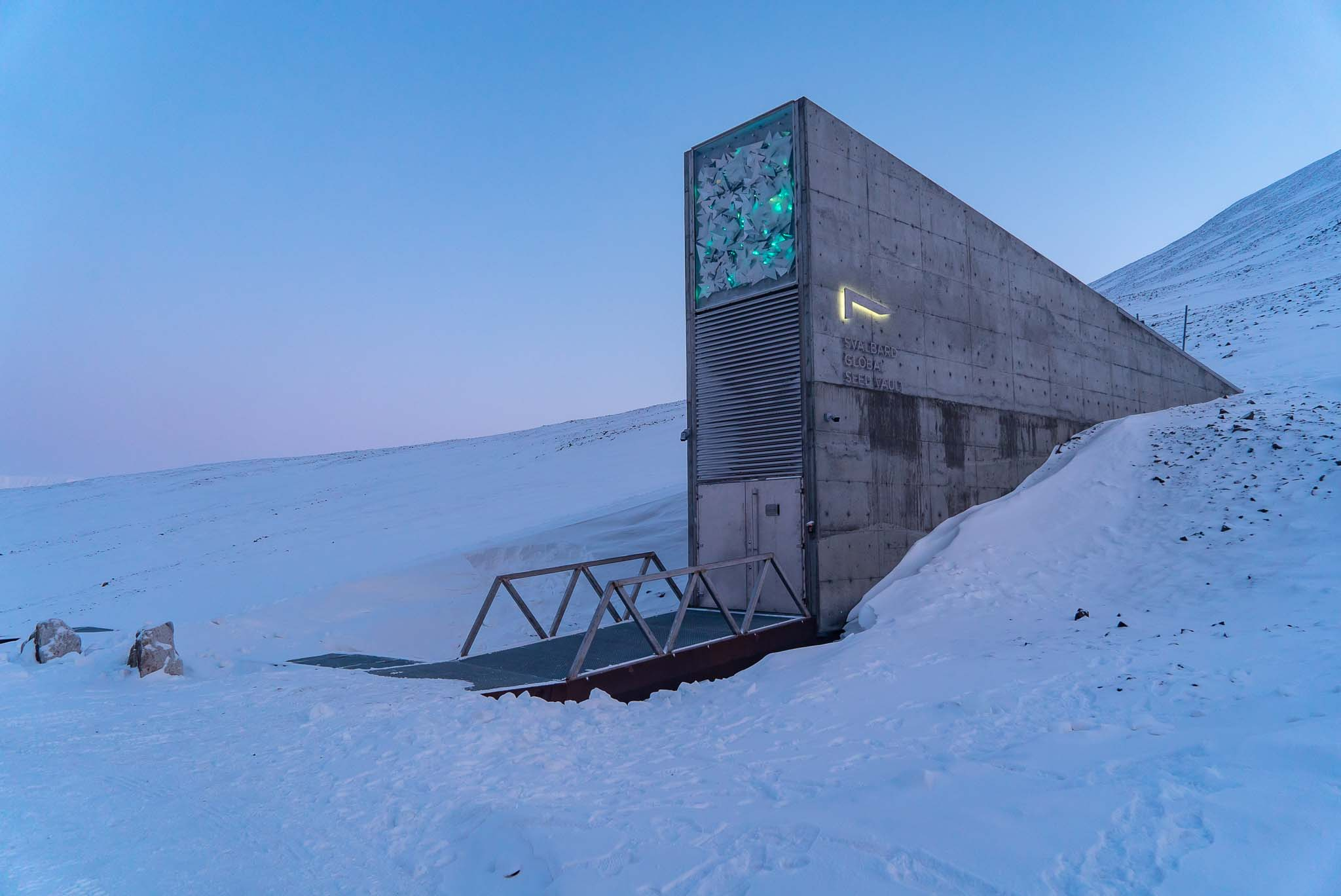 Exterior photo of the Seed Vault in front of a light blue Arctic sky.