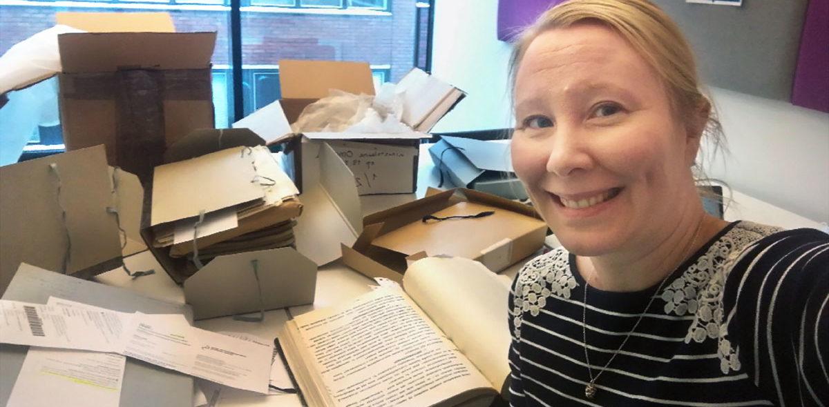 Porträtt av en kvinnlig forskare med ljust hår som sitter vid ett bord med böcker och filer