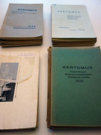 Pöydällä lojuvia vanhoja kirjoja, joissa yhdessä näkyy mustavalkoinen kuva lehmästä