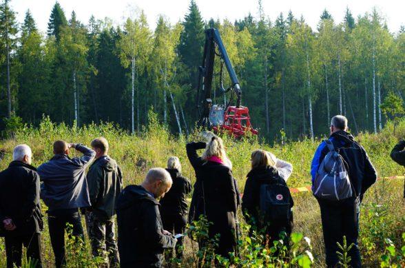 Människor står framför ett kalhygge och ser på en skogsmaskin med stora granar i bakgrunden.