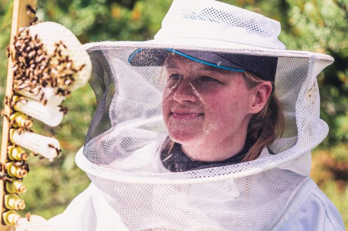 Kvinna iklädd skyddsdräkt betraktar sina bin