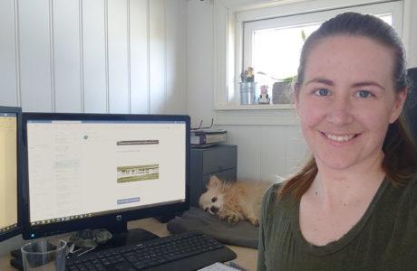 Selfie på hemmakontor forskare Maria Kjetså sitter vid sitt bord framför två skärmar och tittar in i kamerran